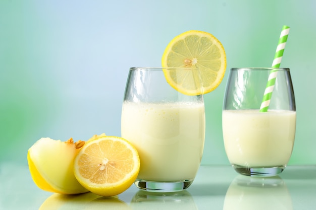 Szklanki z sokiem z melona z mlekiem i sycylijską cytryną na odbijającej powierzchni