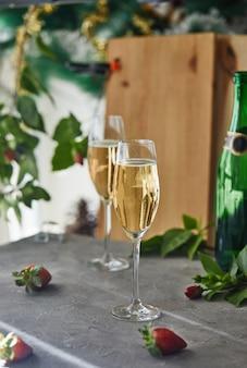 Szklanki z szampanem i truskawkami z zielonymi liśćmi