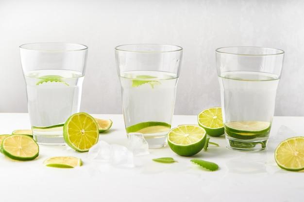 Szklanki z wodą, plasterkami limonki, miętą i kostkami lodu