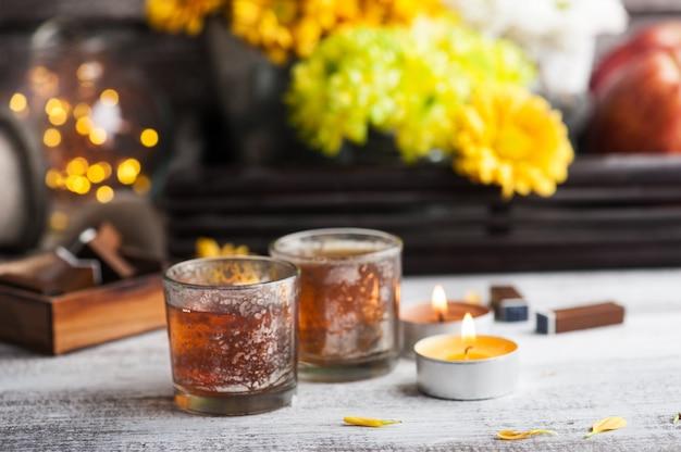 Szklanki z zapalonymi świecami i dzbanek do herbaty