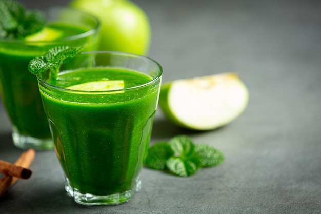 Szklanki zdrowego smoothie z zielonego jabłka obok świeżych zielonych jabłek