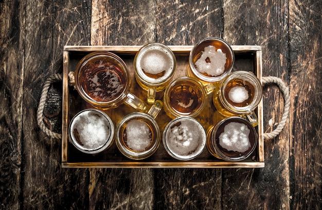 Szklanki ze świeżym piwem na starej tacy na drewnianym stole.