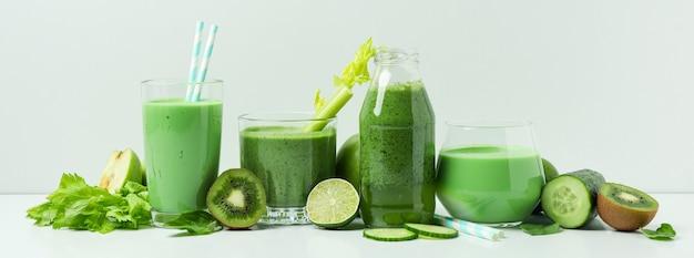 Szklanki zielonego smoothie i składników na białym stole
