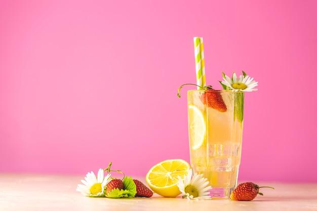 Szklanki zimnego lodowego orzeźwiającego napoju z cytryną i truskawką. jasne różowe tło