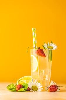 Szklanki zimnego lodowego orzeźwiającego napoju z cytryną i truskawką. jasne żółte tło