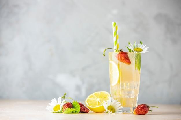Szklanki zimnego lodowego orzeźwiającego napoju z cytryną i truskawką