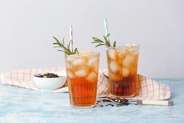 Szklanki zimnej czarnej herbaty z cytryną na kolorowym tle