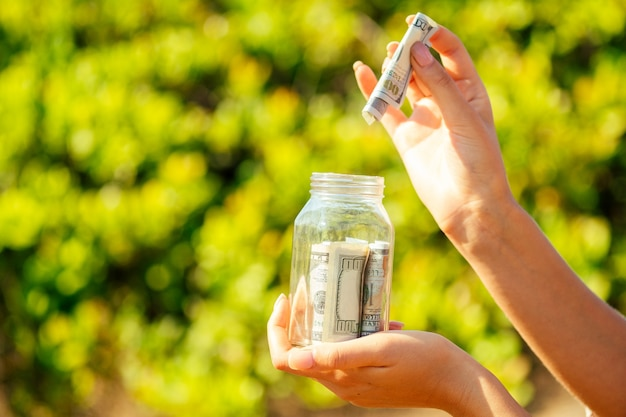 Szklany bank z rachunkami (pieniądze) w rękach na zielonym tle