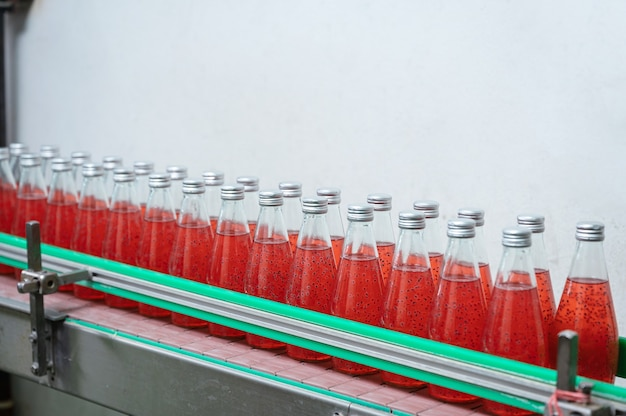 Szklany butelkowany czerwony sok na stalowym przenośniku linii produkcyjnej w fabryce przetwórstwa napojów