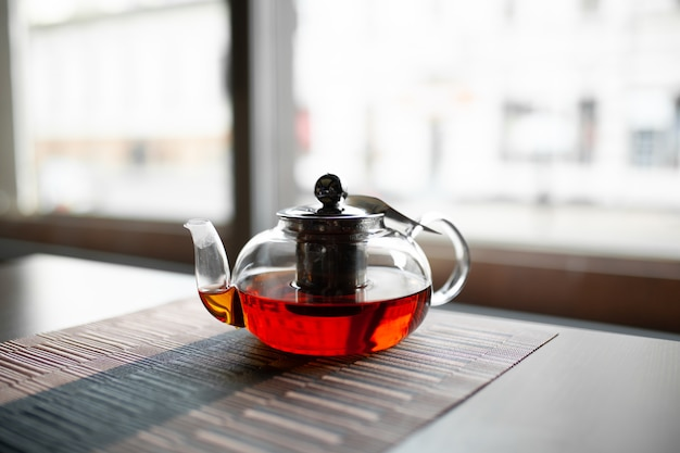 Szklany czajniczek orzeźwiającej świeżej aromatycznej herbaty na drewnianym