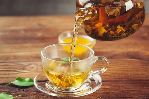 Szklany czajniczek z filiżanką czarnej herbaty na drewnianym stole