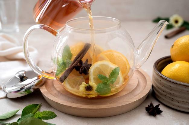 Szklany czajniczek z owocową herbatą cytrusową na jasnym tle. ziołowa pyszna zdrowa ciepła herbata