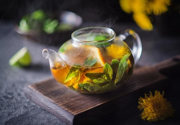 Szklany czajniczek z owocową herbatą ziołową. kompozycja reklamowa: herbata z pomarańczą, miętą, rokitnikiem i ziołami.