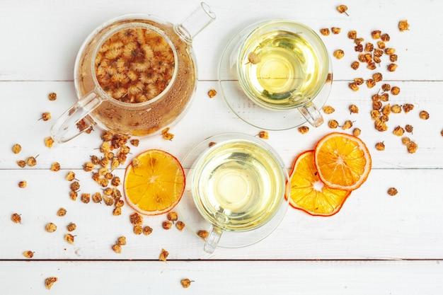Szklany czajnik i filiżanka ziołowa herbata na biały drewnianym