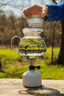 Szklany czajnik napełniony wodą i ogrzewany na gazowym palniku kempingowym.