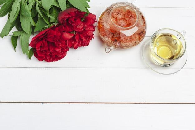 Szklany czajnik ziołowa herbata z świeżymi kwiatami zamyka up