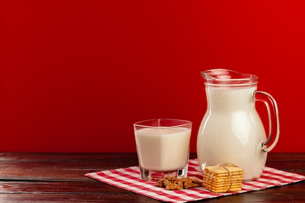 Szklany dzban i kubek mleka na czerwonym tle z ciasteczkami