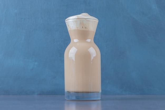 Szklany dzbanek śmietanki latte, na marmurowym tle.