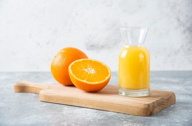 Szklany dzbanek soku z plastrami pomarańczy na desce.