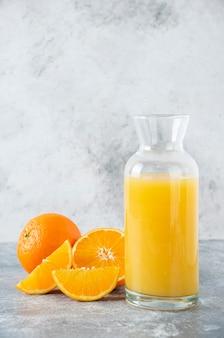 Szklany dzbanek soku z plastrem pomarańczy.