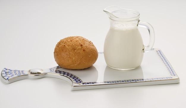 Szklany dzbanek z mlekiem i pieczoną bułką na białym stole, śniadanie
