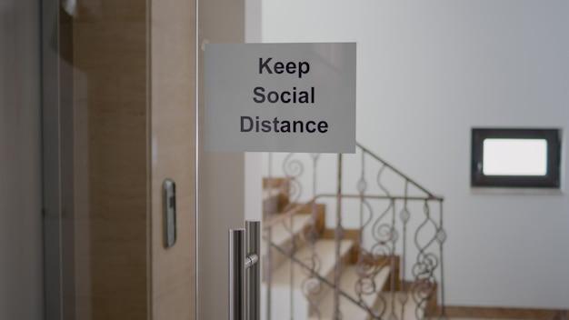 Szklany gabinet z plakatem z zachowaniem dystansu społecznego, nowoczesne schody biurowe związane z pandemią koronawirusa covid 19, globalnym kryzysem gospodarczym.