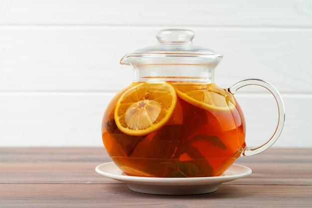 Szklany imbryk z czarną herbatą i kawałkami cytrusów