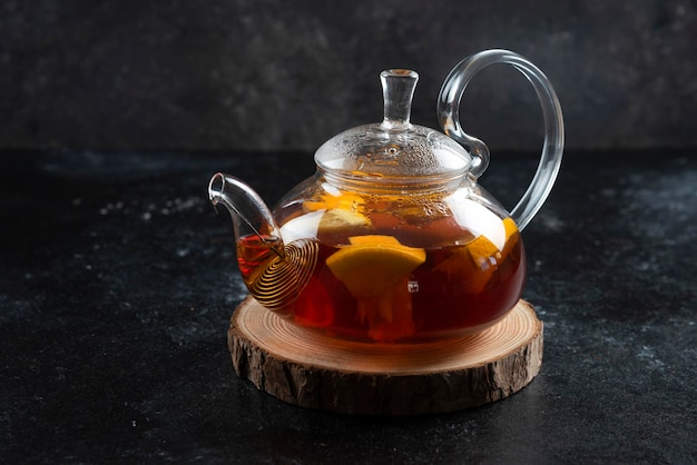 Szklany imbryk z gorącą herbatą i plasterkami cytryny.