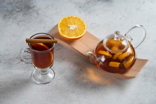 Szklany imbryk z herbatą i plasterkiem pomarańczy.
