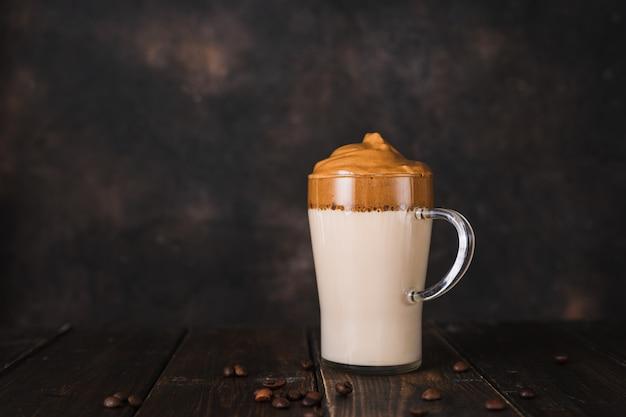 Szklany kubek bitej kawy rozpuszczalnej dalgona na ciemnym tle rustykalnym