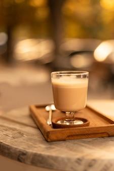 Szklany kubek czarnej kawy z mlekiem i pianką na marmurowym stole