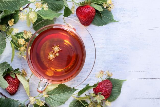 Szklany kubek herbaty lipowej z kwiatami lipy, liśćmi i truskawkami na starym białym drewnianym stole widok z góry. gorący napój dla służby zdrowia.