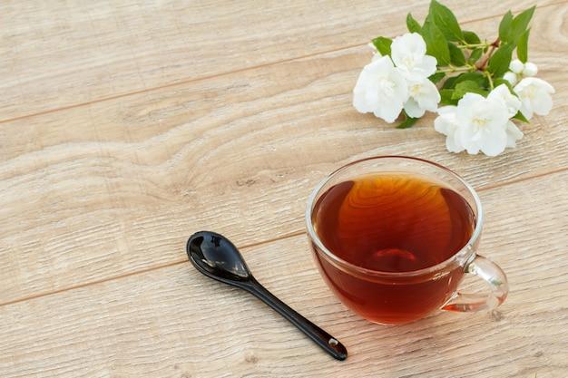 Szklany kubek herbaty, łyżka i białe kwiaty jaśminu na drewniane tła. widok z góry.