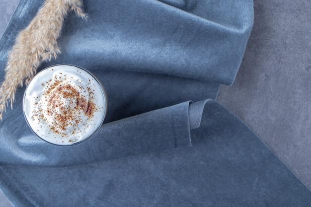 Szklany kubek kawy latte na kawałku tkaniny obok trawy pampasowej, na niebieskim stole.