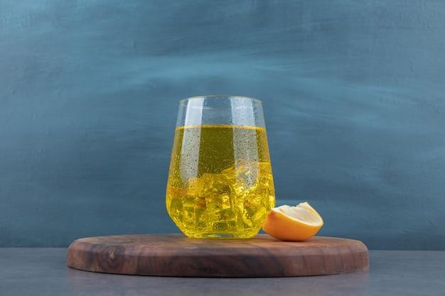 Szklany kubek lemoniady z kostkami lodu i pokrojoną cytryną.