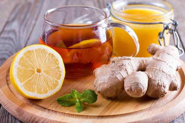 Szklany kubek naturalnej herbaty z imbirem, cytryną, miętą i miodem na drewnianym