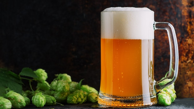 Szklany kubek niefiltrowanego piwa pszenicznego na zardzewiałym tle copyspace i zielonym chmielu