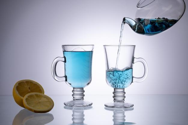 Szklany kubek organicznej niebieskiej anchan na jasnym stole. herbata ziołowa.