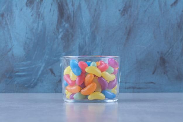 Szklany kubek pełen kolorowych cukierków do żucia.