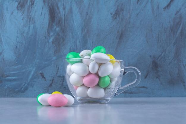 Szklany kubek pełen kolorowych cukierków fasolowych na szarej powierzchni. zdjęcie wysokiej jakości