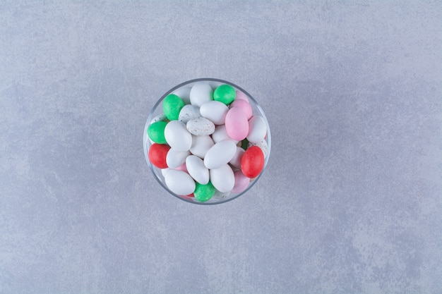 Szklany kubek pełen kolorowych cukierków fasolowych. zdjęcie wysokiej jakości