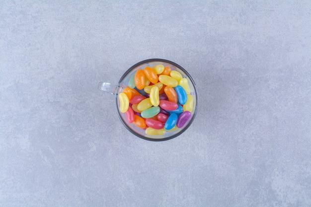 Szklany kubek pełen kolorowych cukierków fasolowych.