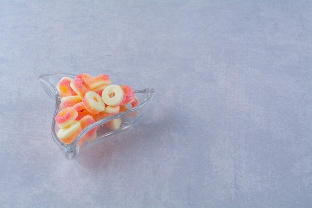 Szklany kubek pełen kolorowych cukierków owocowych. zdjęcie wysokiej jakości