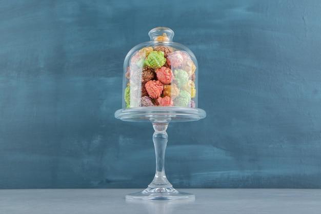 Szklany kubek pełen słodkiego, różnokolorowego popcornu.