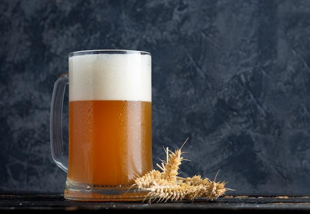 Szklany kubek pszenicznego niefiltrowanego piwa na tle betonowej ściany w pubie z miejsca kopiowania