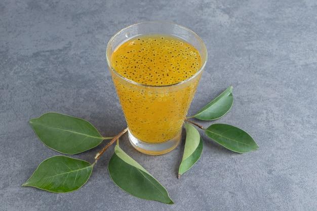 Szklany kubek soku mandarynkowego z liśćmi
