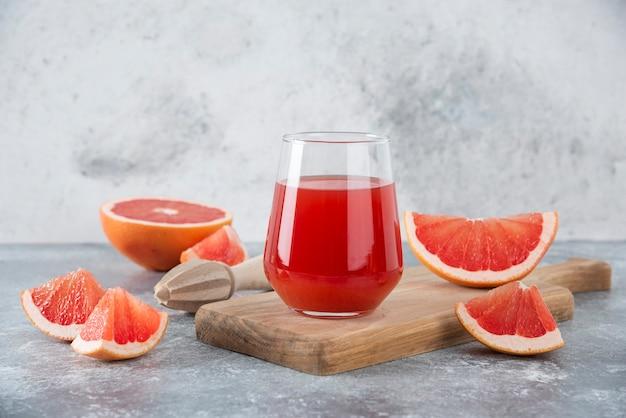 Szklany kubek świeżego soku grejpfrutowego z kawałkami owoców i drewnianym rozwiertakiem.