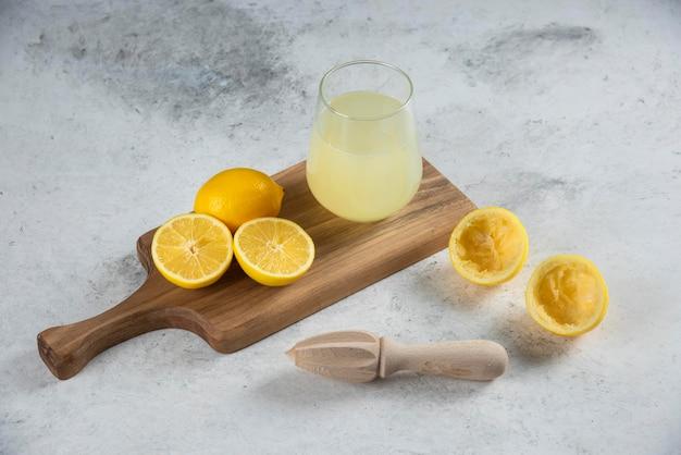 Szklany kubek świeżego soku z cytryny na drewnianej desce.