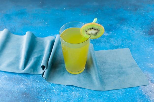 Szklany kubek świeżego soku z plasterkiem kiwi i słomki umieszczony na obrusie.
