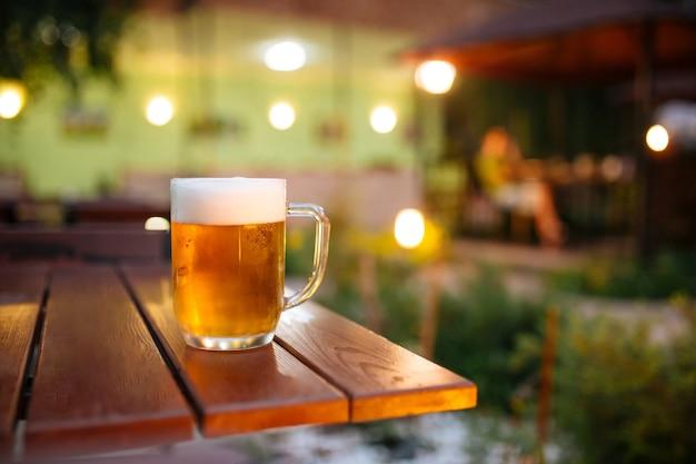 Szklany kubek świeżego zimnego piwa na letnim tarasie